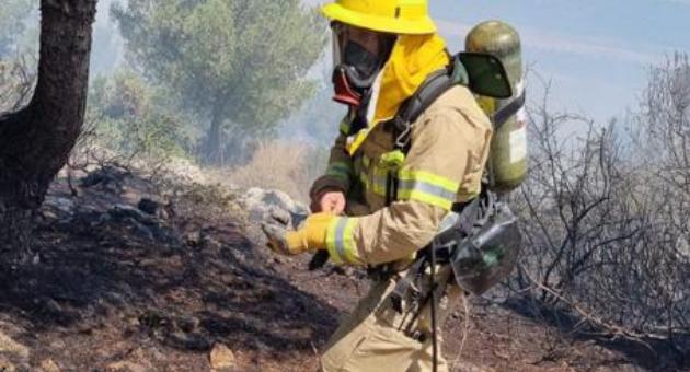 לוחם אש פועל לכיבוי השריפה